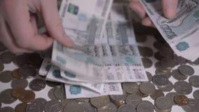 Los escombros y las monedas rusos del dinero sobre las manos blancas de la tabla cuentan la cantidad del hd de la cámara lenta de almacen de video