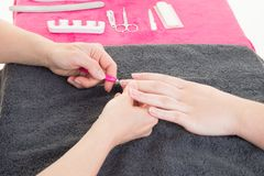Los esmaltes de uñas en la mujer del salón del nailcare que hace el clavo manicure Imágenes de archivo libres de regalías