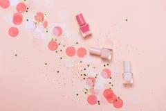 Los esmaltes de uñas y el confeti del rosa en colores pastel, protagoniza y chispea foto de archivo libre de regalías