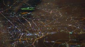 Los espacios abiertos hermosos de la ciudad llenaron de los fuegos de la noche El avión vuela en la noche sobre ciudad Visión aér almacen de video