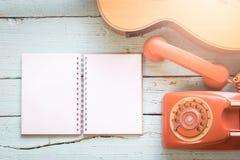 Los espacios en blanco del diario con el teléfono retro y la guitarra acústica Fotos de archivo libres de regalías