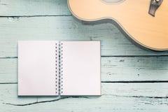 Los espacios en blanco del diario con una guitarra acústica Fotografía de archivo libre de regalías