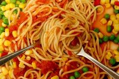 Los espaguetis cocinados sirvieron con la salsa de tomate y la mezcla vegetal fotos de archivo libres de regalías