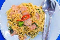 los espaguetis con tocino, la salchicha y la albahaca curruscantes fritos se van, caliente y picante comida, cocina internacional Fotos de archivo