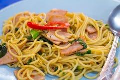 los espaguetis con tocino, la salchicha y la albahaca curruscantes fritos se van, caliente y picante comida, cocina internacional Foto de archivo