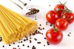 Los espaguetis mienten en un fondo blanco, junto con los tomates de cereza imagen de archivo