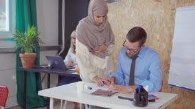 Los especialistas del hombre y de la mujer están discutiendo el contrato en la oficina, corrigiendo metrajes