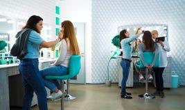 Los especialistas del maquillaje y del corte de pelo preparan a las muchachas modelo para un desfile de moda fotografía de archivo
