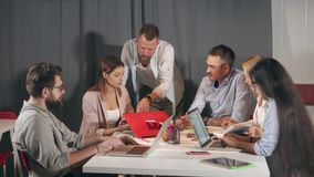 Los especialistas están discutiendo idea e informes en la reunión de negocios en compañía joven almacen de metraje de vídeo