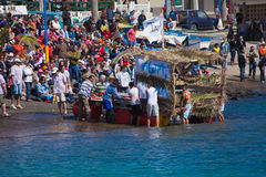 Los espectadores miran como los participantes para llevar el agua adentro anualmente Foto de archivo libre de regalías