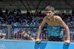 Los espectadores miran a través y sobre de una cerca para ver la acción de lucha en el festival de lucha del aceite turco de Kirk Fotos de archivo
