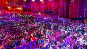Los espectadores recolectan en el auditorio y miran la demostración en timelapse del teatro Pasillo grande con los asientos rojos metrajes