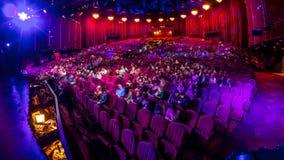 Los espectadores recolectan en el auditorio y miran la demostración en timelapse del teatro Pasillo grande con los asientos rojos