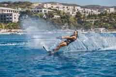 Los esquíes acuáticos se deslizan en las ondas, atleta de sexo femenino en el Mar Egeo, Grecia Foto de archivo
