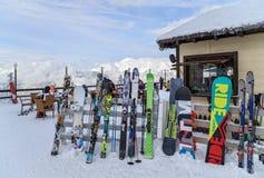 Los esquís y las snowboard se inclinan contra una cerca del café del invierno Imagen de archivo