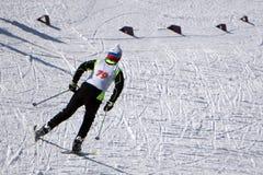 Los esquiadores de los deportes corren en los esquís en ropa del invierno imagenes de archivo