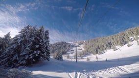 Los esquiadores del esquí ascienden por el remonte de la telesilla a lo largo de la pista almacen de video