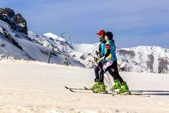 Los esquiadores en las montañas se mueven síncrono Foto de archivo