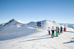 Los esquiadores miran al tablero de la información en el top de la montaña Imágenes de archivo libres de regalías