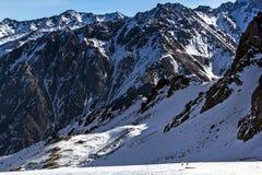 Los esquiadores montan en el pie de las montañas rocosas Fotografía de archivo