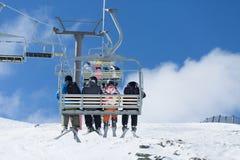 Los esquiadores montan la elevación de silla del esquí Imagen de archivo libre de regalías