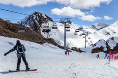 Los esquiadores que se colocan en el esquí nevoso del cirque de la montaña se inclinan en el día soleado contra el fondo del invi Fotografía de archivo