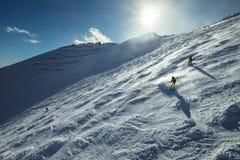 Los esquiadores van abajo de la colina nevosa de la montaña Foto de archivo