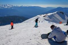 Los esquiadores y los snowboarders antes descienden en la pista del esquí Imágenes de archivo libres de regalías
