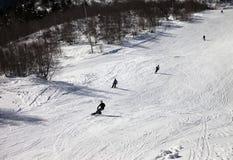 Los esquiadores y los snowboarders en el esquí se inclinan en el día de invierno del sol Fotografía de archivo