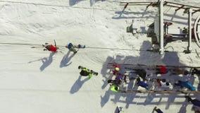 Los esquiadores y los snowboarders aéreos van encima de la elevación en la cuesta almacen de video