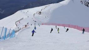 los esquiadores y los snowboarders No-identificables en ropa brillante montan en la cuesta nevosa de una estación de esquí de la  almacen de video