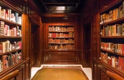 Los estantes con los viejos volúmenes de libros y antiquewooden la tabla dentro de la biblioteca real Fotos de archivo