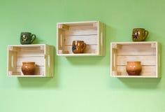 Los estantes hechos de cajas de madera con la arcilla ruedan Imagen de archivo