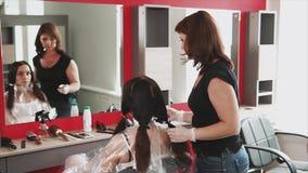 Los estilistas por el pelo preparan el pelo de un cliente joven del salón de belleza para colorear almacen de video
