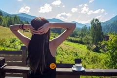 Los estiramientos de la muchacha, mirando el sol y las montañas de la mañana Al lado de ella, en la verja del balcón, es una taza imagen de archivo libre de regalías
