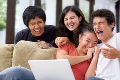 Los estudiantes étnicos multi se divierten con la computadora portátil Foto de archivo libre de regalías