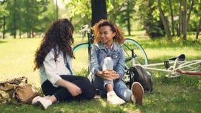 Los estudiantes alegres afroamericano y caucásico son que hablan y de risas de sentarse en parque en césped después de montar las metrajes