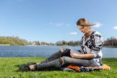 Los estudiantes aprenden durante el tiempo agradable en un lago Imágenes de archivo libres de regalías