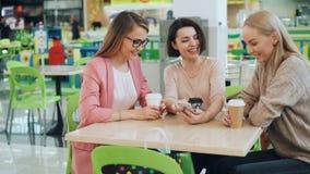 Los estudiantes apuestos están utilizando la sentada del smartphone en café junta y están mirando hacer de la pantalla entonces a almacen de metraje de vídeo