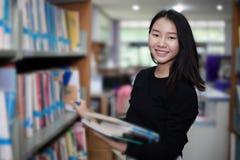 Los estudiantes asiáticos que se sostienen para la selección reservan en biblioteca imagen de archivo