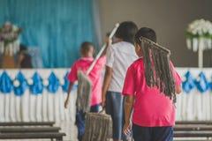 Los estudiantes ayudan a frotar el piso imagen de archivo