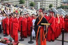 Los estudiantes chinos y extranjeros con una bendición del hanfu recolectaron en la torre de reloj en la ceremonia Foto de archivo libre de regalías