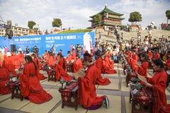 Los estudiantes chinos y extranjeros con una bendición del hanfu recolectaron en la torre de reloj en la ceremonia Imágenes de archivo libres de regalías