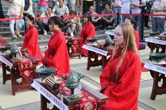 Los estudiantes chinos y extranjeros con una bendición del hanfu recolectaron en la torre de reloj en la ceremonia fotografía de archivo