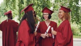 Los estudiantes compañeros son que hablan y de risas después de la ceremonia de graduación que sostiene diplomae y que lleva los  almacen de video