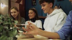 Los estudiantes comparten sus impresiones y las discuten el sentarse en una tabla con los libros en un café Las adolescencias lle almacen de metraje de vídeo