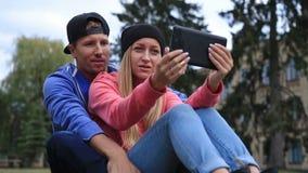 Los estudiantes comunican con la charla video en la tableta metrajes