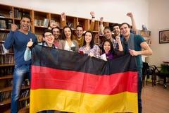 Los estudiantes con las manos aumentadas y que sonríen hacen frente al actual coun alemán imagen de archivo libre de regalías
