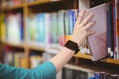 Los estudiantes dan con el libro de la cosecha del smartwatch del estante Imagen de archivo