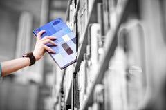 Los estudiantes dan con el libro de la cosecha del smartwatch del estante Imágenes de archivo libres de regalías
